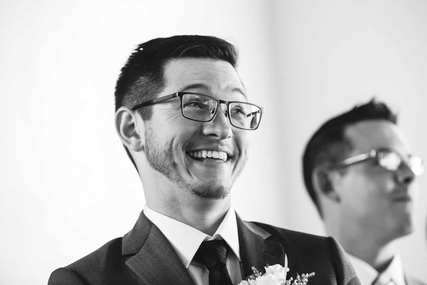 a groom grins ear to ear as his bride walks down the aisle.