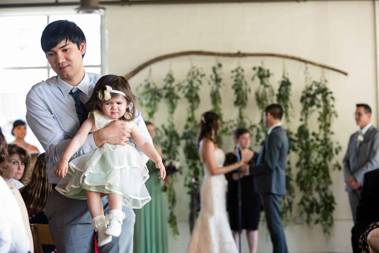 a grumpy looking flower girl gets carried by her father while the ceremony goes on.