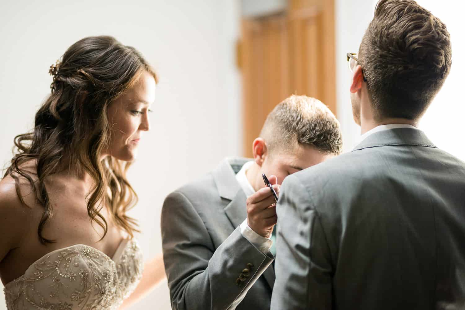 a groomsman cuts open a pocket on his suite.