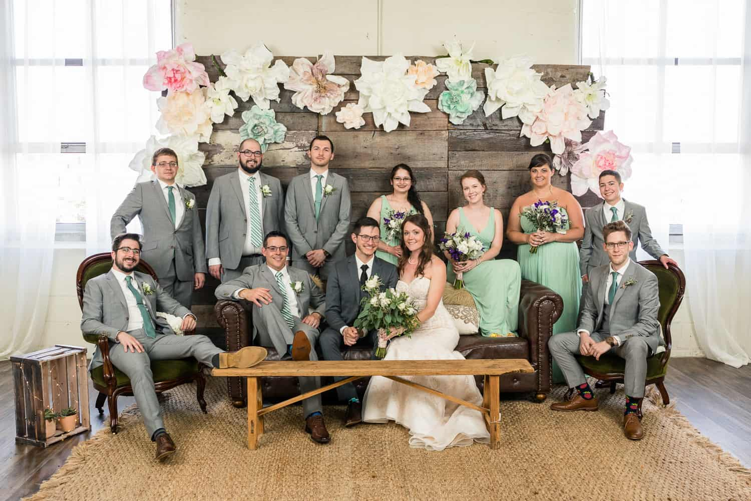 a wedding party portrait at arbor loft. there are large paper flowers above the people.
