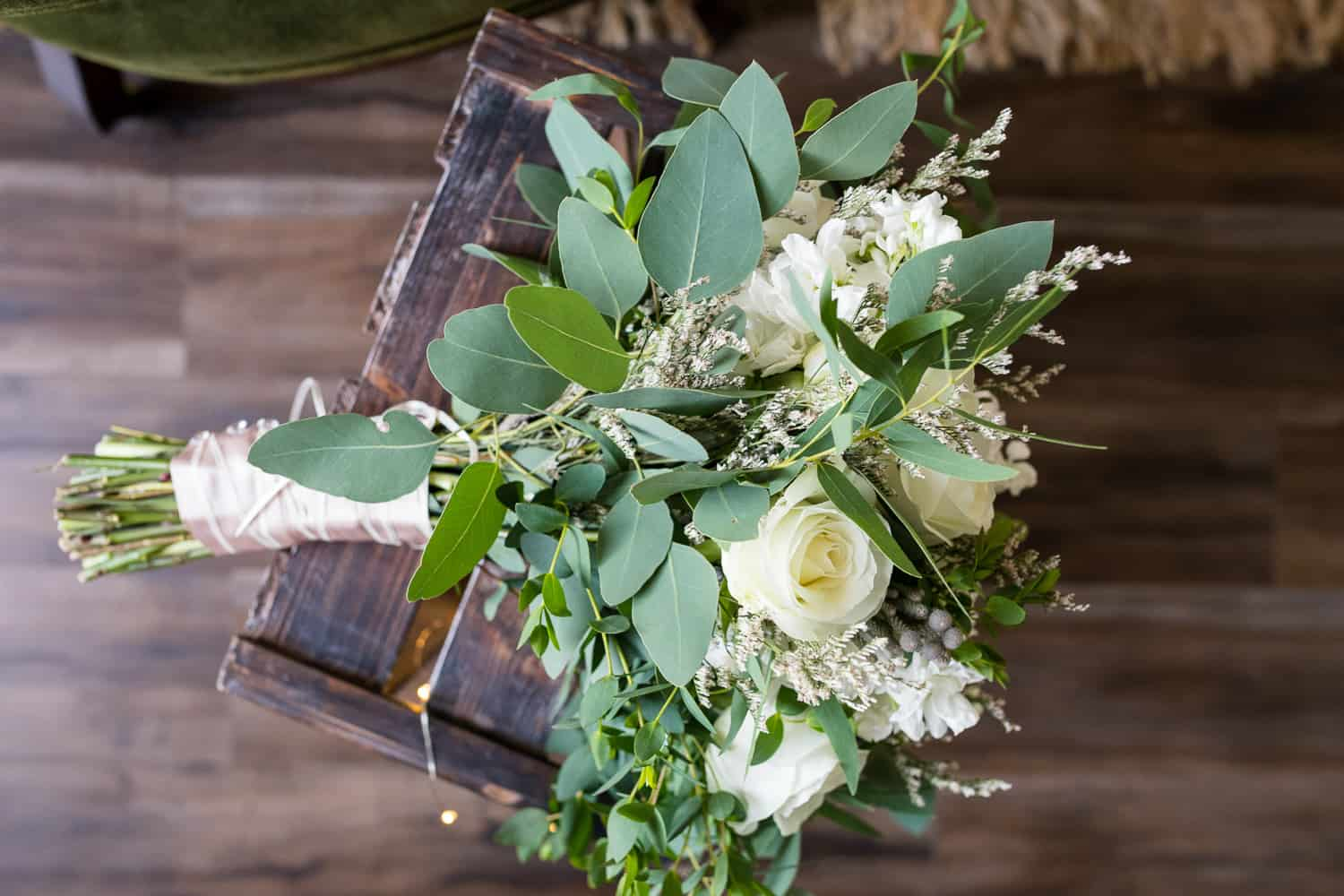 brides bouqet with white roses and hydranga sitting on a wooden crate.