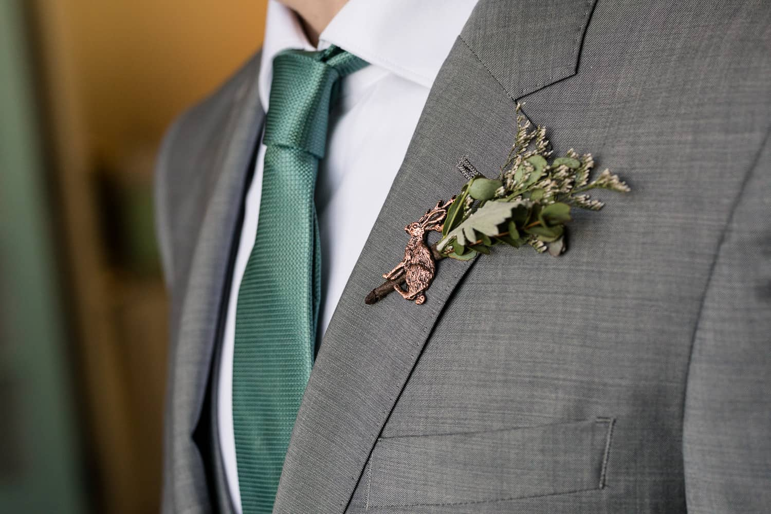 boutonniere with greenery and a jackolope pin