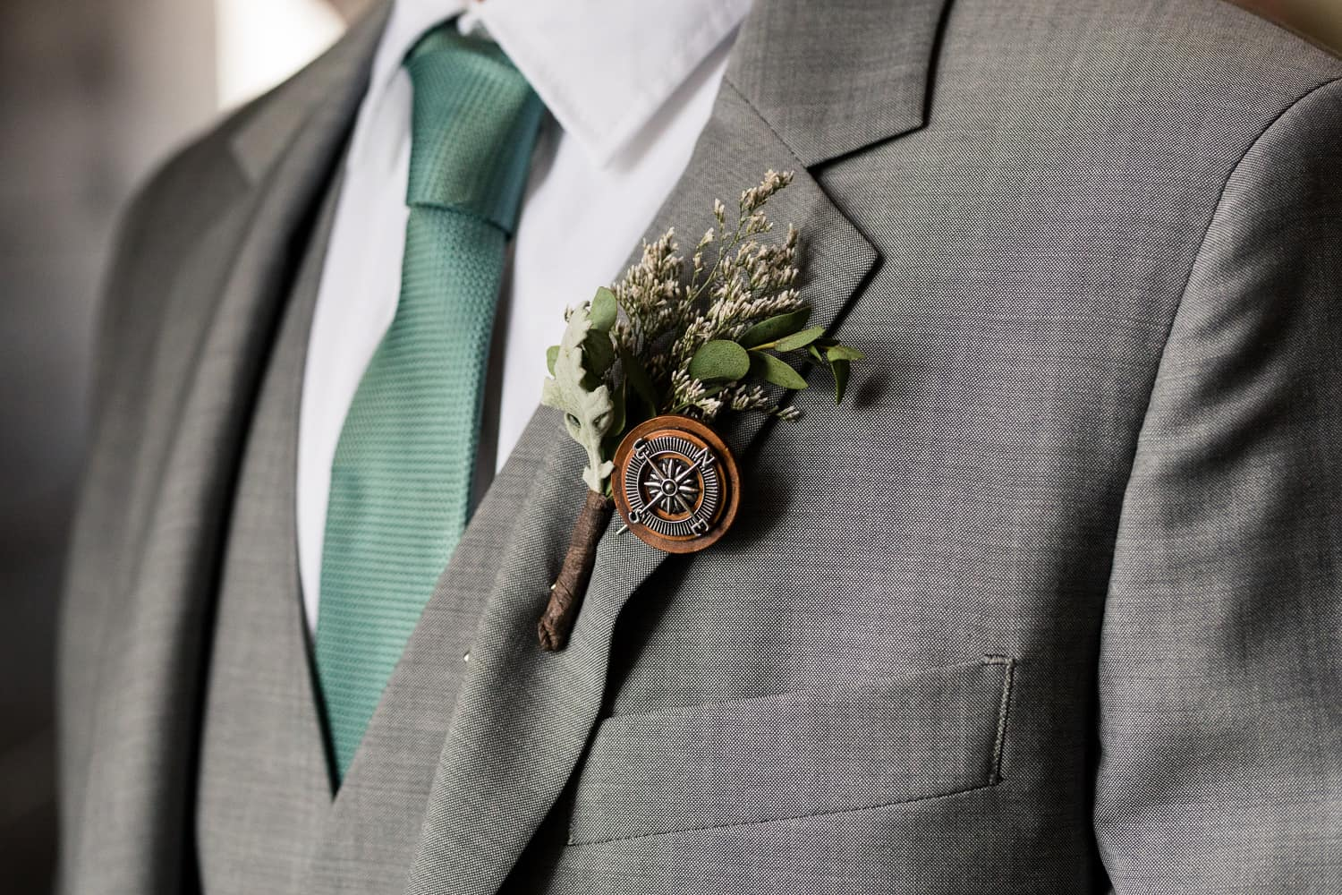 boutonniere with a compass pin.
