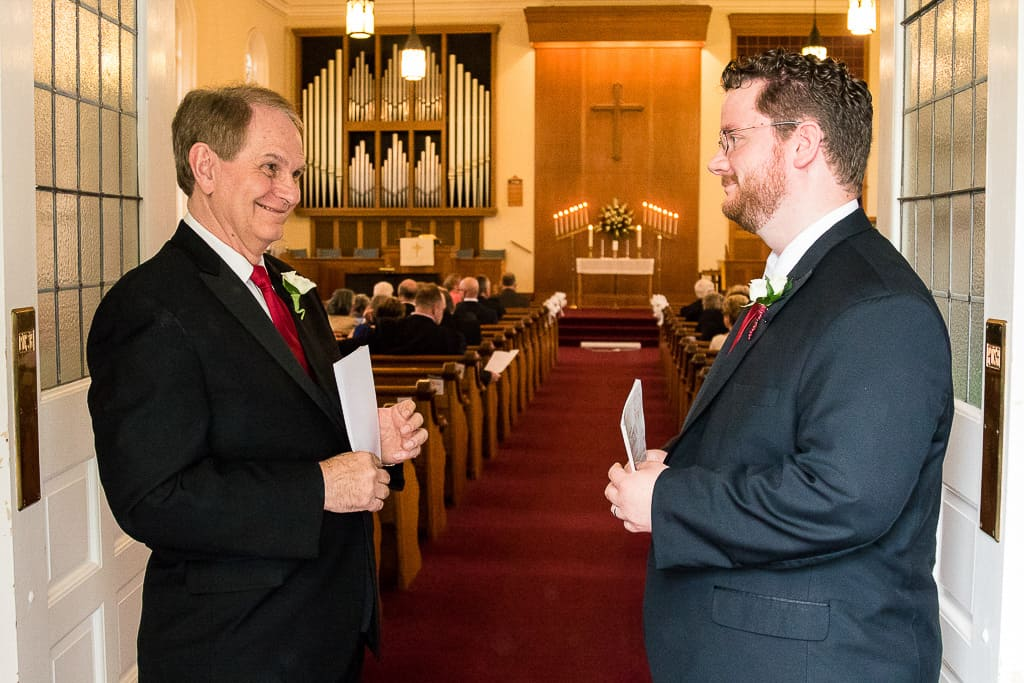 Bride's brother and father laugh in church entrance.