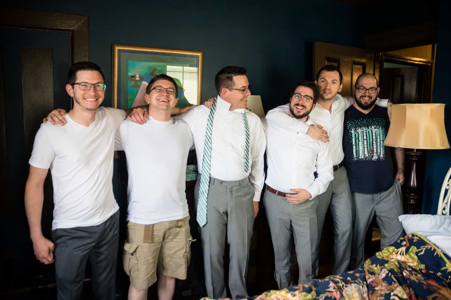 the groomsmen all line up with their arms around each other.