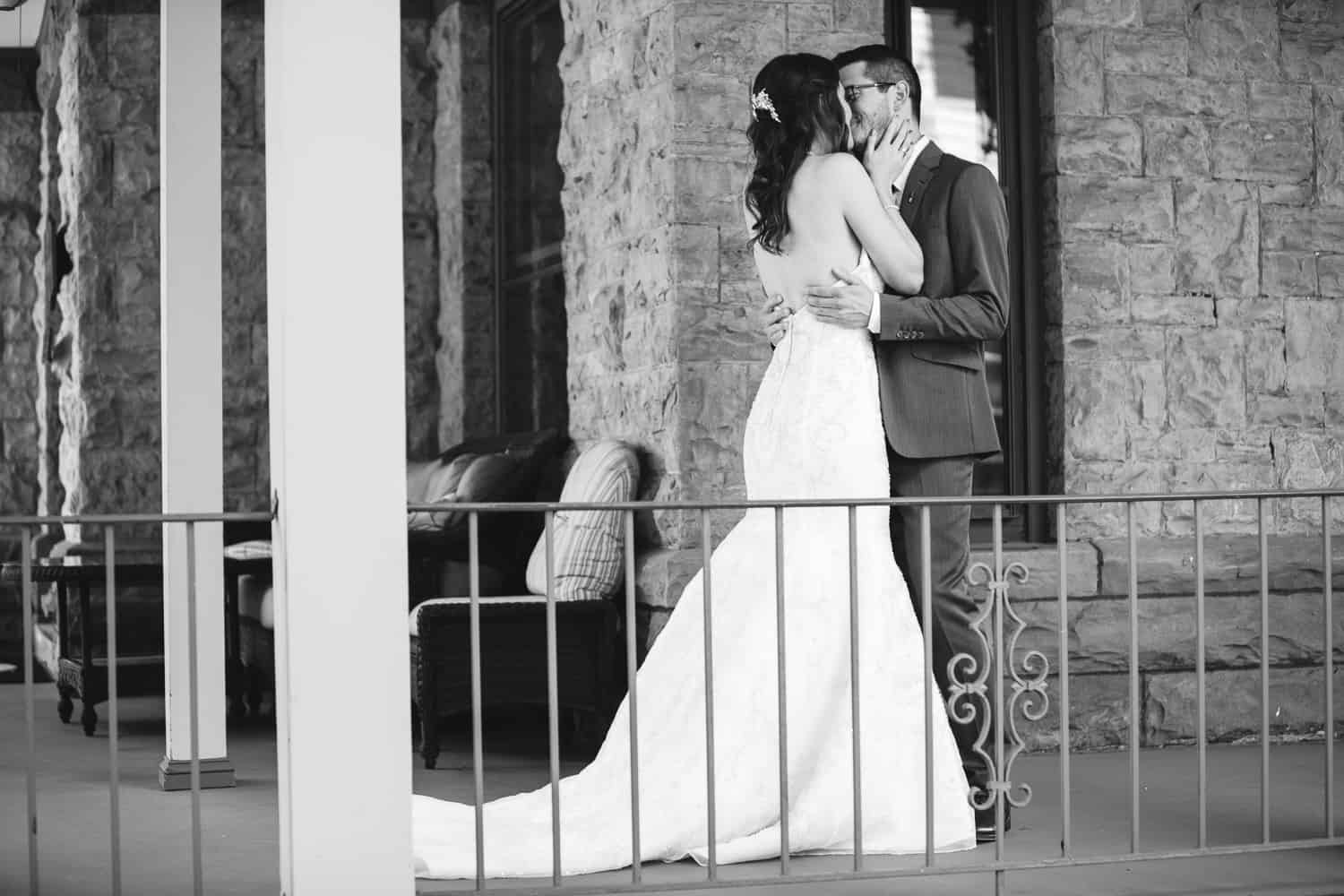 black and white photo of the bride and groom doing their first look on a porch.