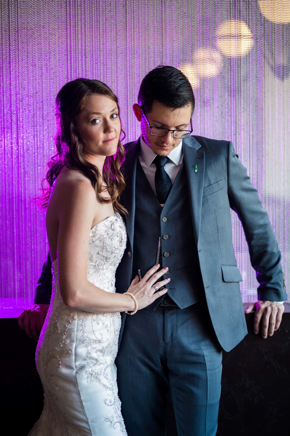 bride and groom stand infront of a curtain of metal beads which is colored purple with a flash.