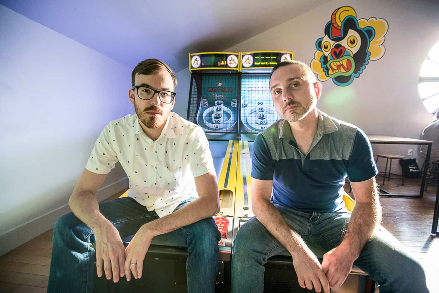 Event portrait of Splyce co-founders Vincent and Charlie sitting on ski ball game.