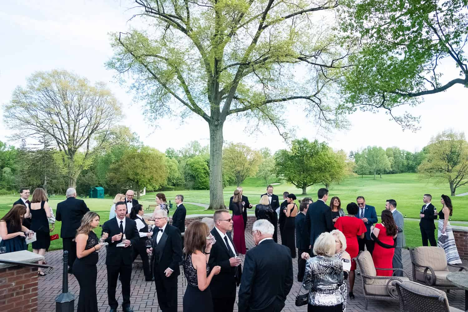 Event photograph of guests standing on patio at Oak Hill Country Club.