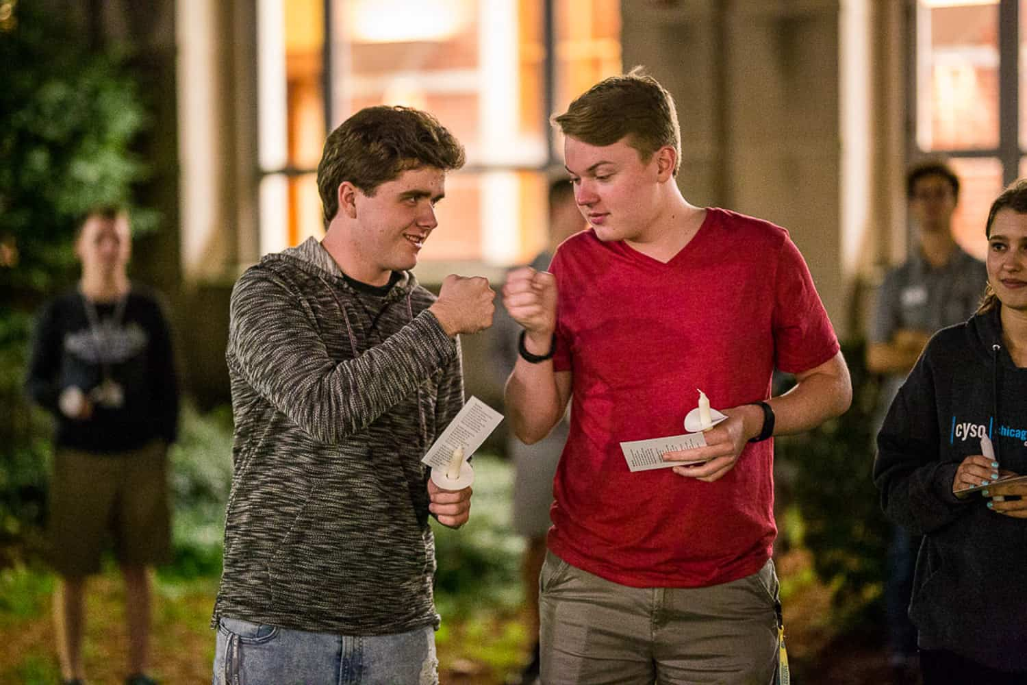 Photograph two friend sfist bumping at the Eastman School of Music candlelight ceremony event.