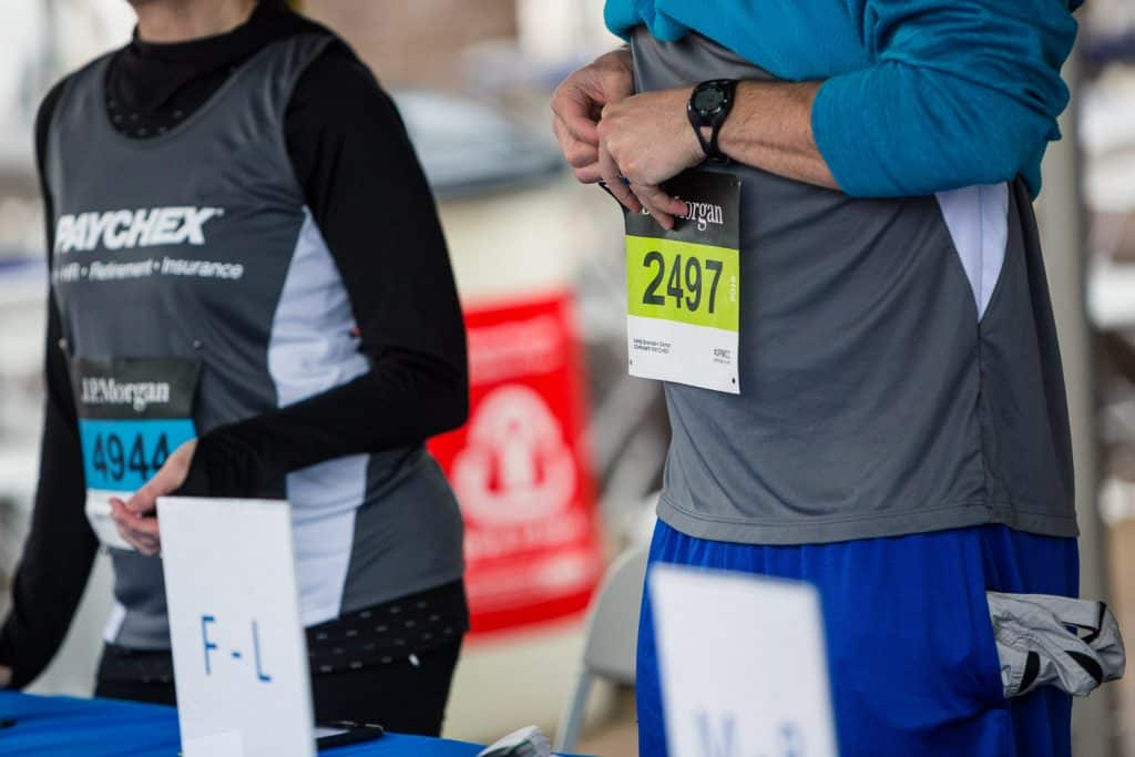 Event photography of a runner pinning their number at Chase Corporate Challenge.