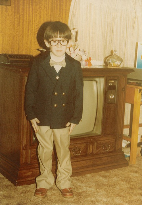 4 yr old me standing in front of a 1980's wooden tv console.