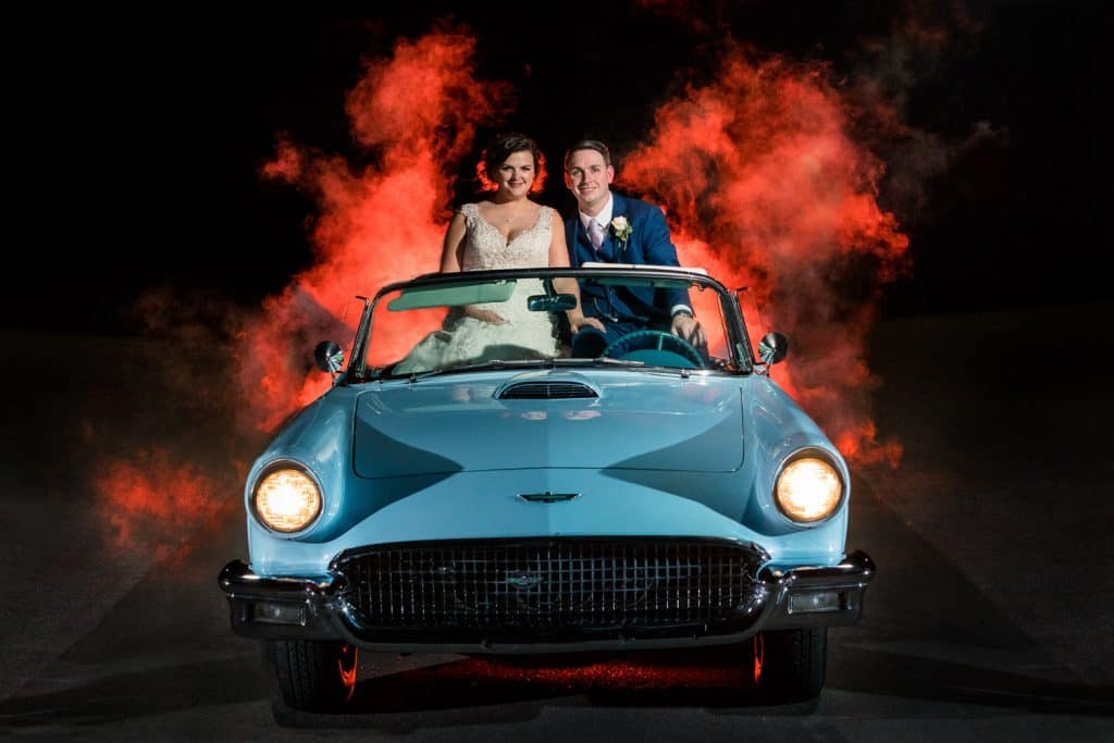 Chris and Tessa pose for wedding portrait at Bristol Harbour in a classica Thunderbird.