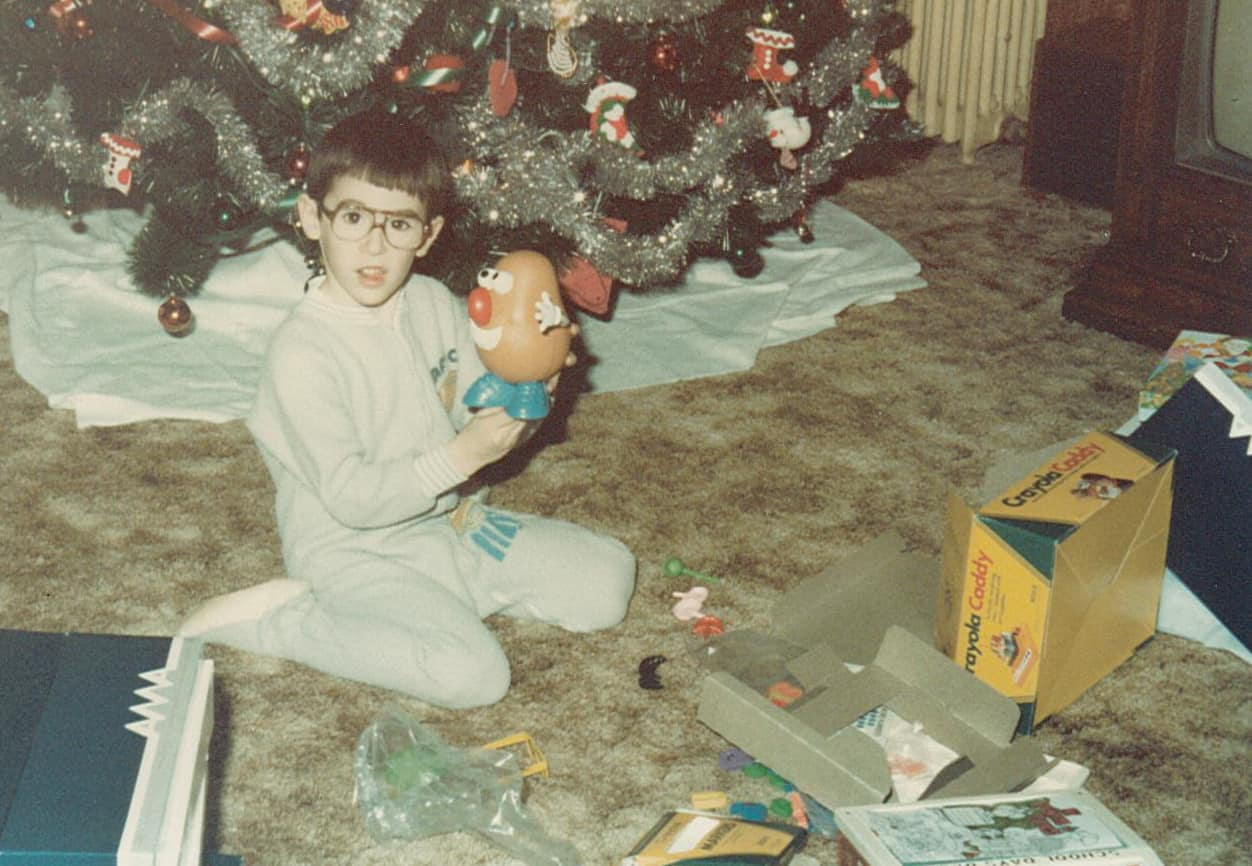 4 or 5 yr old John in a PJ onsie holding Mr. Potato head on Christmas.