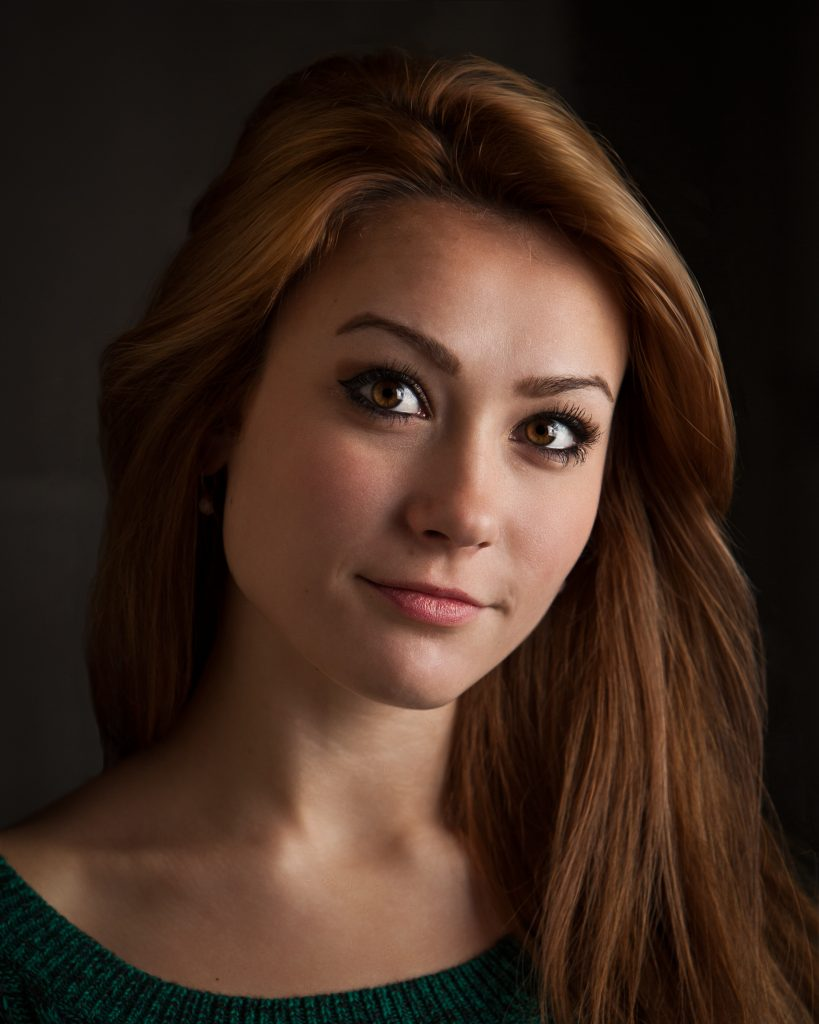 Professional headshot of a young red headed actress.