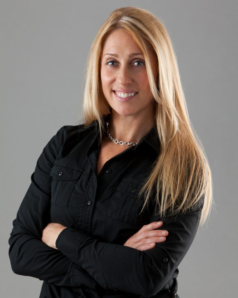 Professional headshot of a trainer with arms crossed.