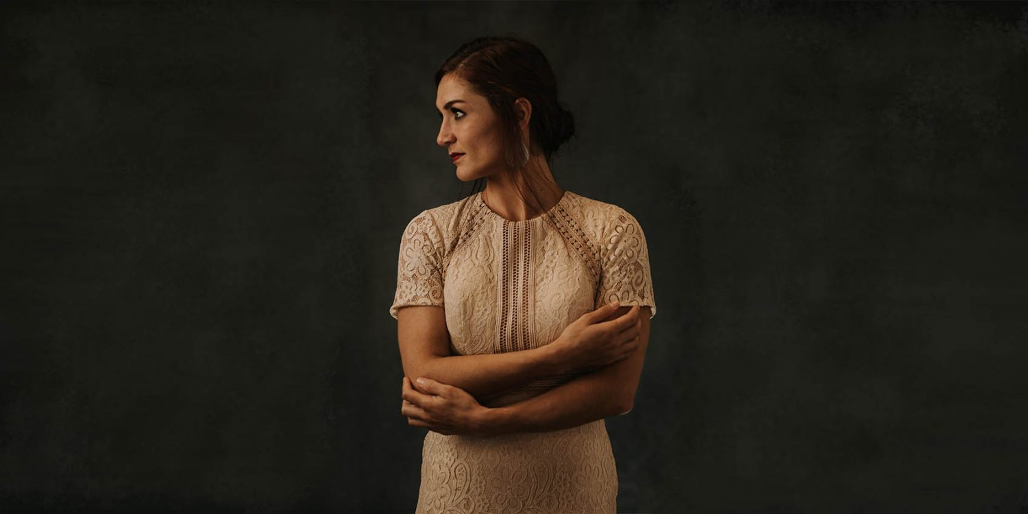 A header image featuring a woman with brown hair, standing with arms crossed.