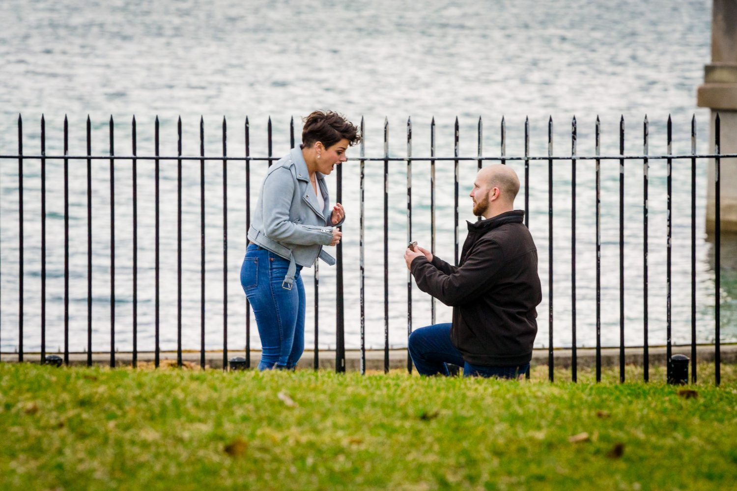 A man in a black jacket proposes to his girlfriend near the highland park resovoir.