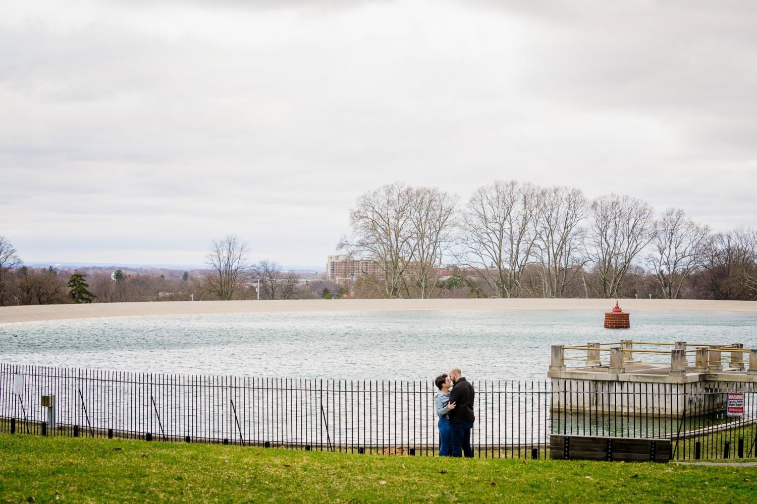 A man in a black jacket kisses his girlfriend near the highland park resovoir.