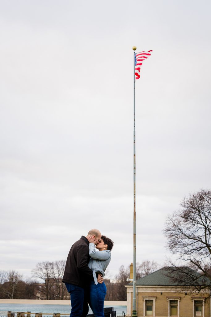 A man in a black jacket kisses to his fiance near the highland park resovoir.