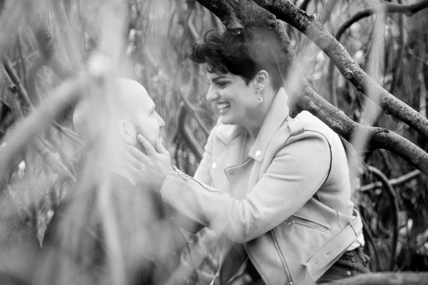 A black and white photo of a newly engaged couple. They are sitting in a tree.