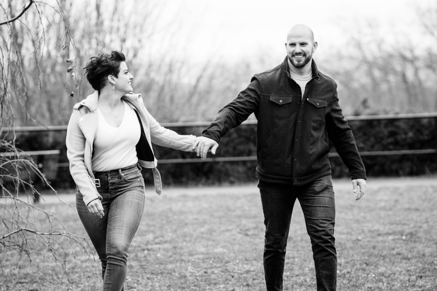 A black and white photo of a newly engaged couple. They are walking happily.