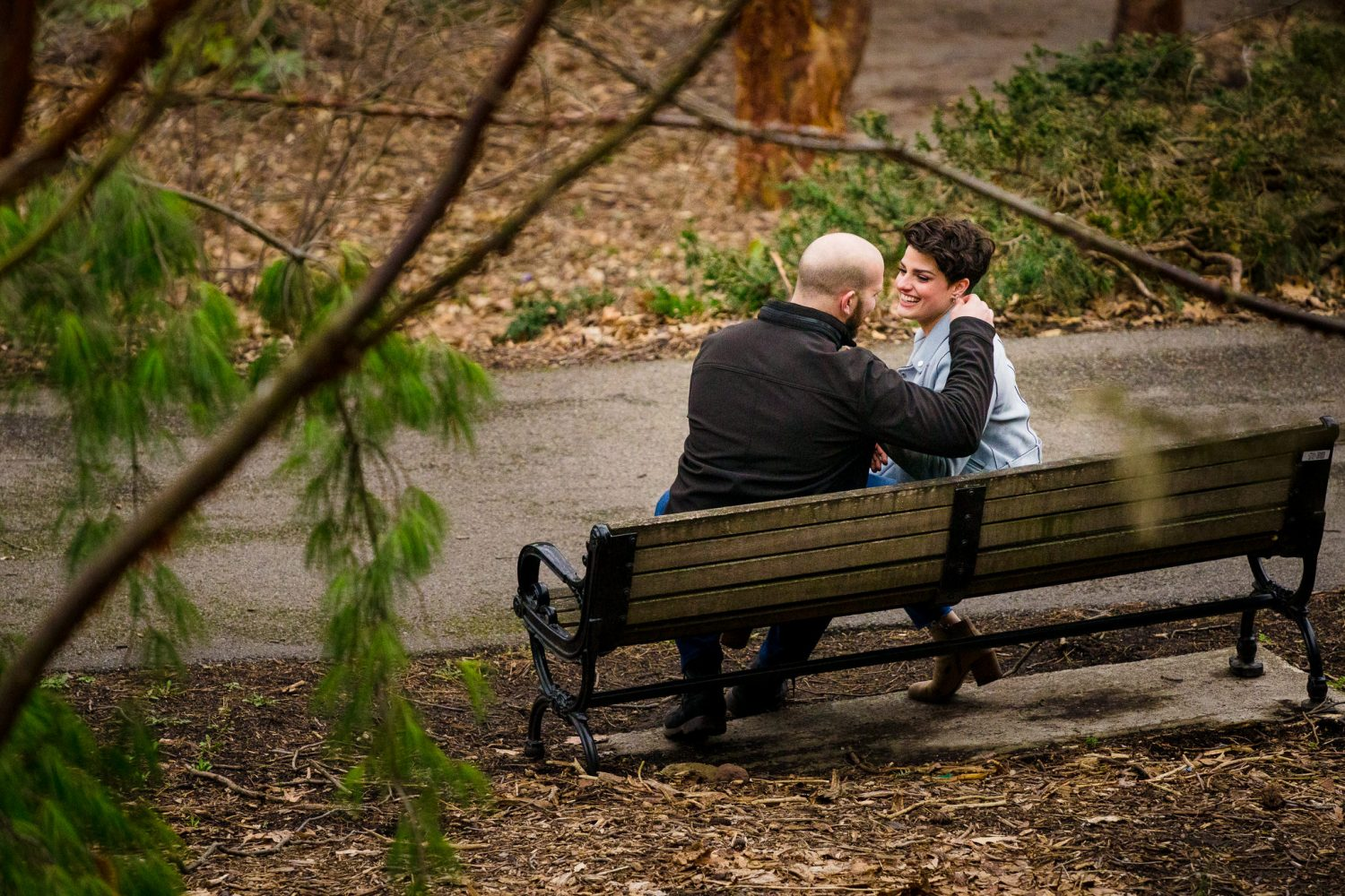 A newly engaged couple sit on a bench in highland park.