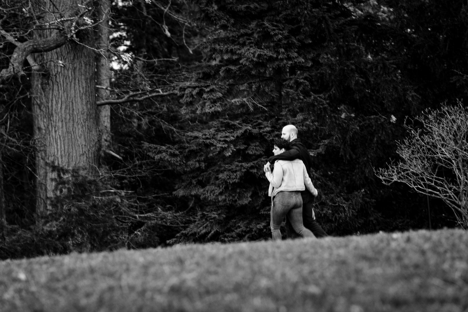 A black and white photo of a man and his girlfriend walking, he is about to propose.