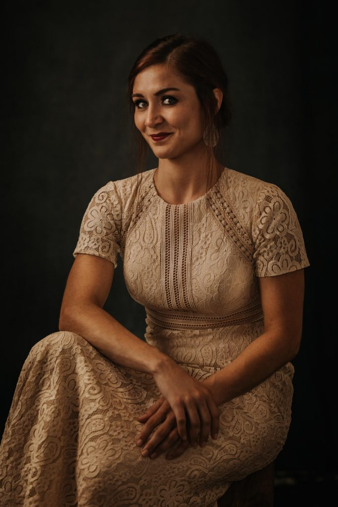 A brunette woman in a lacey dress sitting with her arms crossed.