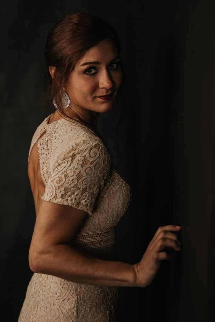 A brunette woman in a lacey dress standing against a wall with hand on wall.